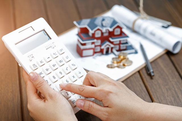 a-female-hand-operating-a-calculator-in-front-of-a-villa-house-model_1387-886