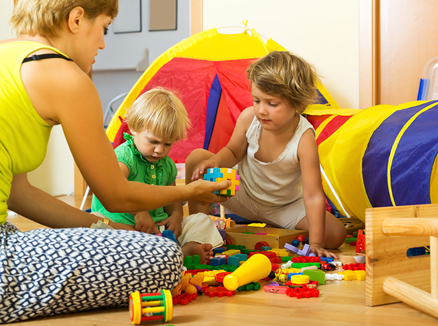 Woman with short hair and two siblings together playing with  toys indoor